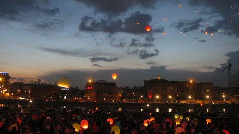 Many heavenly small lanterns fly to night sky against floating clouds, time lapse