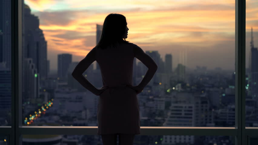 Elegant, young woman admire sunset from window at home