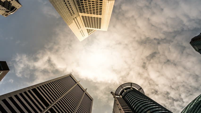 Time lapse - Looking up to business and financial skyscraper buildings in Singapore with moving clouds and sun in the sky at Singapore central financial district