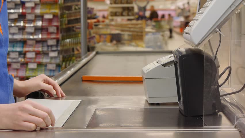 cashier counts money in supermarket