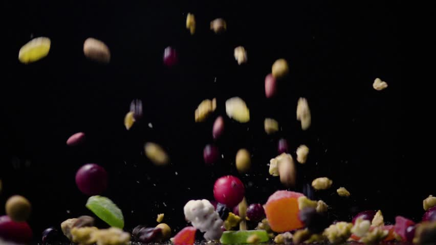 A mixture of dried fruits and nuts with muesli falls on a table on a black background from above slow motion | Shutterstock HD Video #24632090