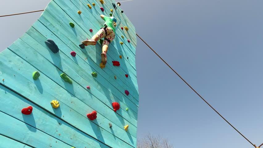 BANSKO, BULGARIA - 20 AUGUST, 2016: A little girl climbs up on an climbing wall