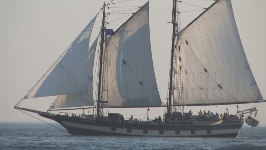 tall ship cruising in the ocean during sunset