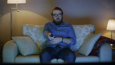 Portrait Shot of a Man Sitting on a Sofa in His Living Room, Watching TV, Changing Channels. Floor Lamps are Turned ON. Shot on RED EPIC-W 8K Helium Cinema Camera.
