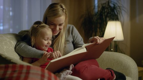 Mother and Her Cute Daughter are Sitting On a Couch in the Living Room. They're Reading Children's Book. It's Evening. Shot on RED EPIC-W 8K Helium Cinema Camera.