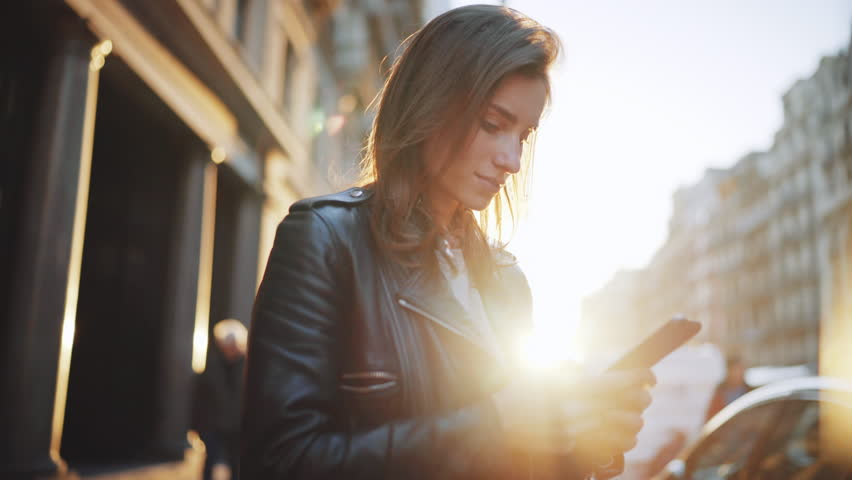 Attractive young woman walking at the sunny city streets and chatting with friends, joyful hipster girl using cellphone outdoors, sunset background | Shutterstock HD Video #24654356
