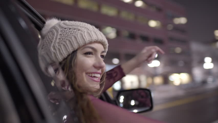 Carefree Young Woman Leans Out Car Window At Night In Downtown, She Waves To People, Raises Her Arms In The Air With Excitement