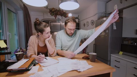 Worried young family looking at their bills in the kitchen at home. Man and woman calculating domestic accounts.