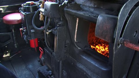 Vintage steam train: shoveling coal from the tender into the engines firebox. Steam Locomotive Jung 23071 (1956)
