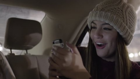 Happy Young Woman Takes Photos Of Her Friend In Backseat Of Moving Car In City At Night