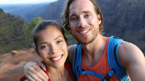 Couple taking selfie video having fun on hike on Hawaii. Woman and man in love taking candid selfportrait while on hiking travel in Waimea Canyon State Park, Kauai, Hawaii, USA.