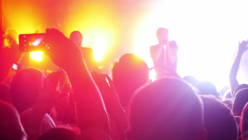 Fans cheering in audience waving their hands and hold mobile phones with digital displays the crowd at a rock concert. 3840x2160 | Shutterstock HD Video #24762893
