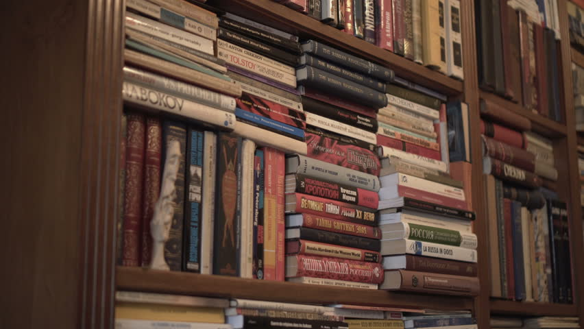 man reading book in front of bookshelf looking and searching. man searching library for right book. russian classic writers. russian revolution book and encyclopedia