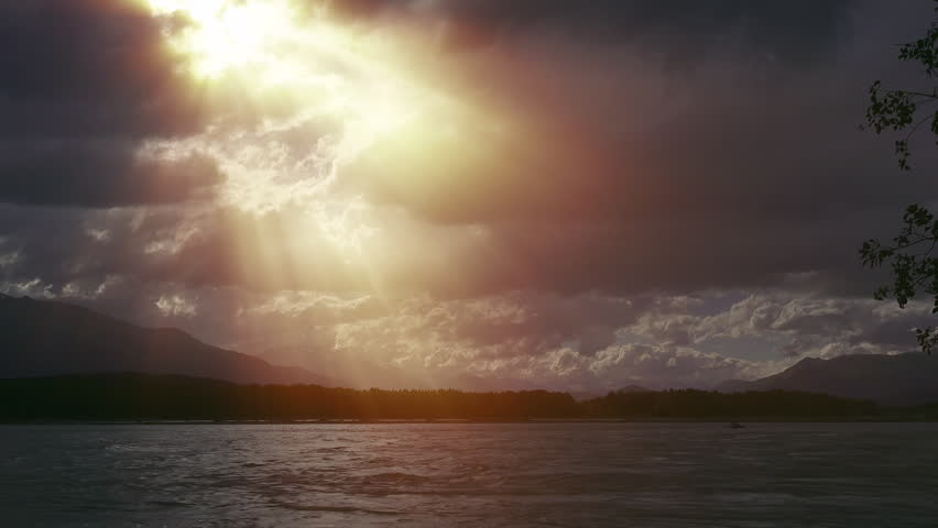 Intense Beaming God Rays through Opening In Stormclouds after Storm over Floodwater River