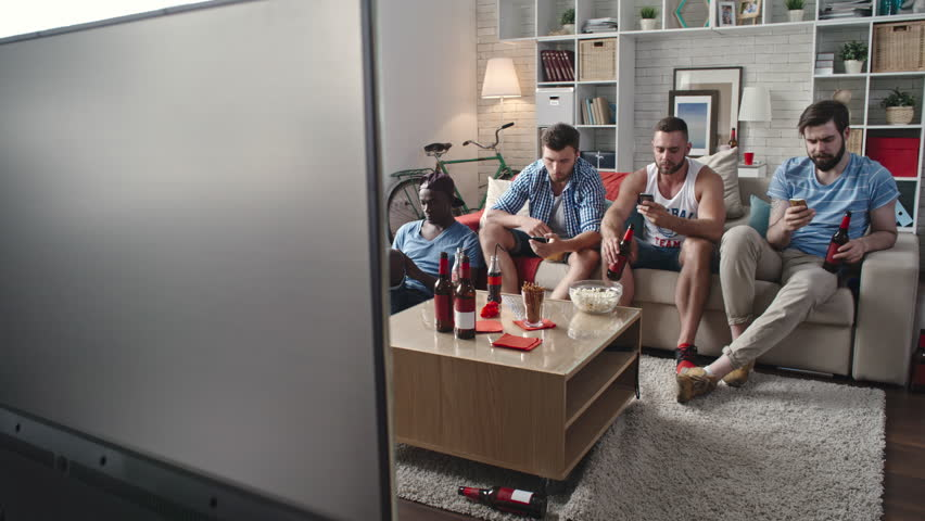 Friends sitting together on couch at home and browsing the Net on their smart phones while watching live football on TV