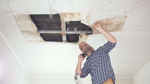 Young man call on the phone in the Service, and public utilities. Ceiling panels damaged huge hole in roof from rainwater leakage.Water damaged ceiling , Insurance case.