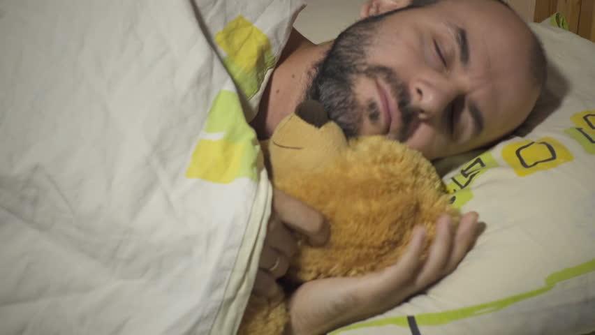 Adult male sleeping and hugging teddy bear.