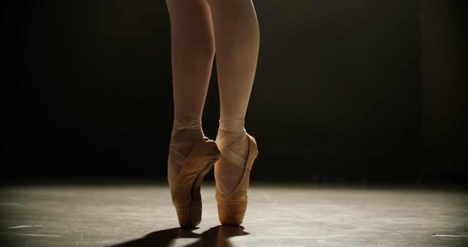 Close-up of ballerina feet in pointe shoes dancing ballet elements, slow motion, dark background
