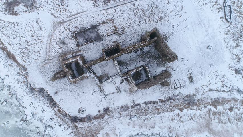 Over the top view of the old Toolse castle being surrounded with lots of snow on the ground in Lahemaa park