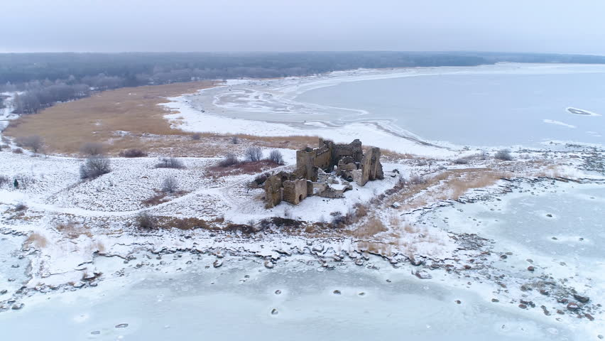 Panoramic view of the Toolse castle in Estonia with lots of snow surrounding the small ruined castle and the frozen sea on a winter season
