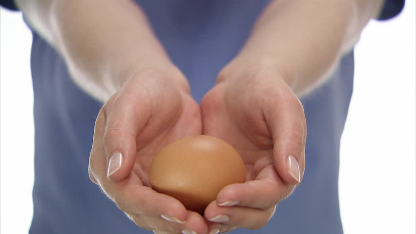 An egg in the hands of a woman, close-up. | Shutterstock HD Video #2486360