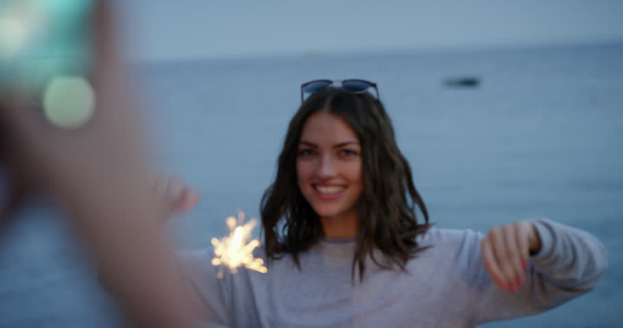 Young woman taking photo of best friend holding sparklers dancing in slow motion celebrating new years eve and independence day with fireworks at sunset on beach with ocean background