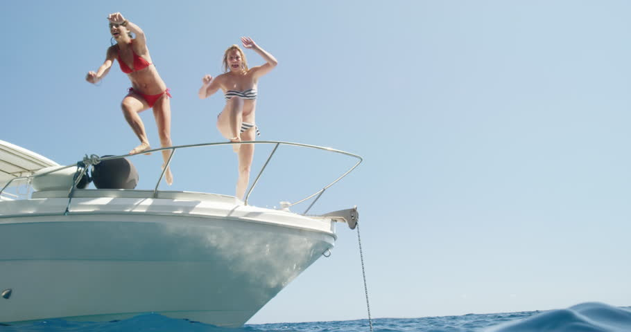 Women jumping off boat into ocean two girls jump into clear blue water from sailboat enjoying active lifestyle summer holiday travel vacation adventure | Shutterstock HD Video #24912911