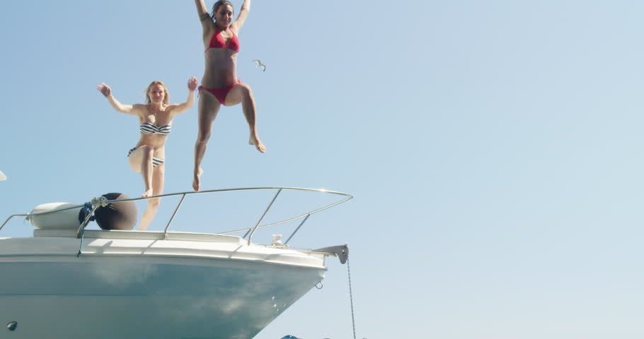 Women jumping off boat into ocean two girls jump into clear blue water from sailboat enjoying active lifestyle summer holiday travel vacation adventure #24913460