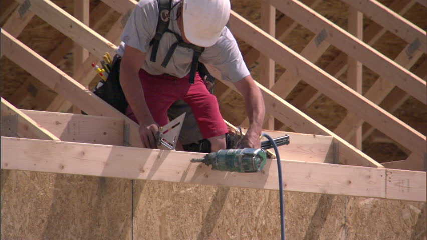 Construction worker nails together rafters of a new home.