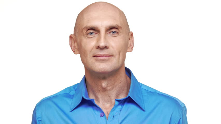 Middle-aged bold Caucasian male in blue shirt standing on white background and smiling
