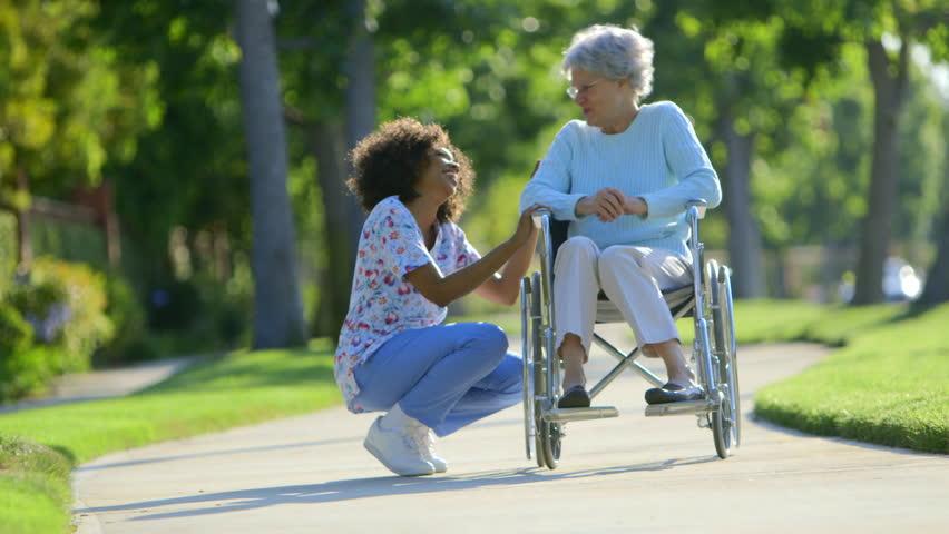 Nurse talking with elderly woman in wheelchair
