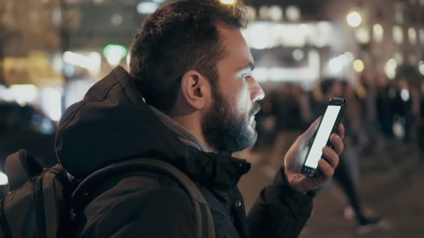 A young man is commuting to work while browsing his cellphone on a busy urban street at night. 100fps slowmotion.
