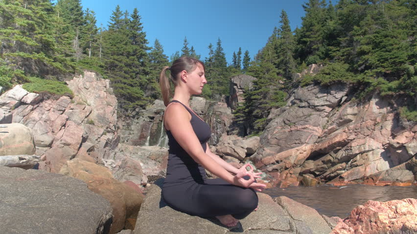 CLOSE UP: Attractive young woman meditating sitting on red volcanic rocky shore and enjoying relaxing sunny spring day. Girl relaxing doing meditation by the seashore in lush overgrown wilderness