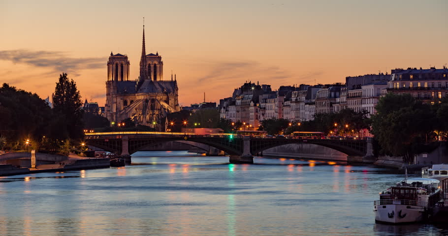 Notre Dame de Paris Cathedral, Ile Saint Louis and the Seine River at twilight. Time lapse of a summer evening with city lights and the Sully Bridge in the 4th Arrondissement of Paris. France