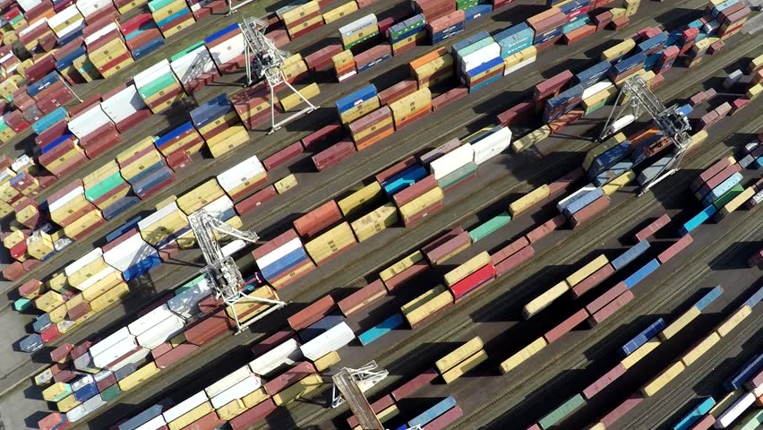 Aerial top down view flying over container terminal showing many intermodal containers used for freight transport shipping goods stacked up on each other different colors cranes moving in between 4k | Shutterstock HD Video #24960080