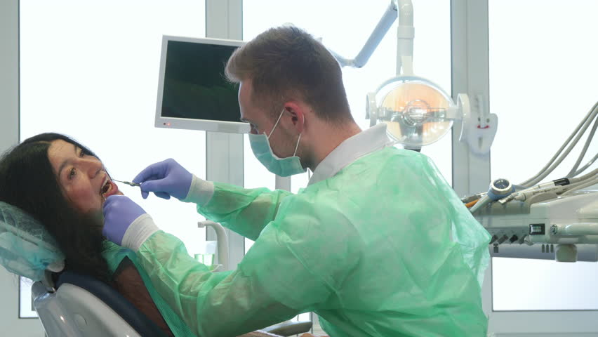 Young Caucasian Dentist Examining Patients Teeth Male -5116
