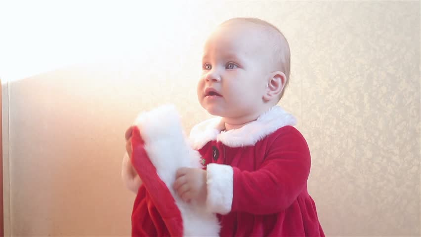 The baby in Santa Claus costume holds a Santa's cap. | Shutterstock HD Video #24971510