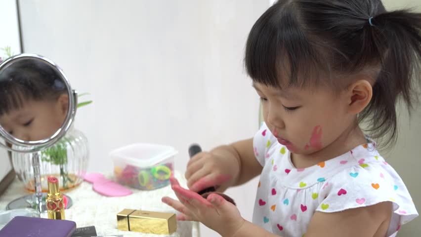 A cute little girl asian with mess lipstick all over face | Shutterstock HD Video #24999050