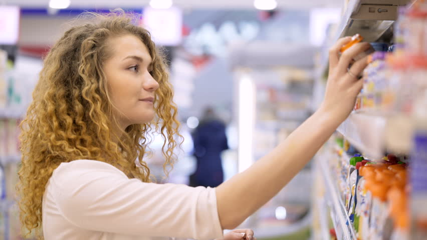 Cute 20s blonde lady with long curly hair makes purchases in department store close up. Young mother select puree, juices for child and put baby food in basket holding hand. Natural complexion closeup