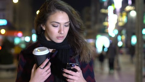 NIS, SERBIA, NOVEMBER 2016: Young beautiful woman standing downtown at night. Holding Apple iPhone smart phone and coffee to go.
