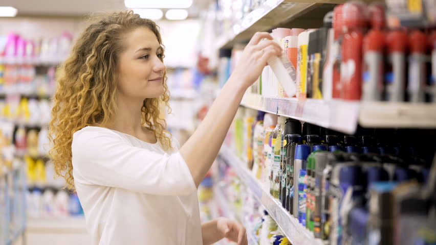Beautiful woman looking at cosmetics in supermarket. Female Choosing Body Care Products In Mall. Shopping in the store | Shutterstock HD Video #25025144
