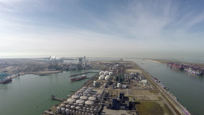 Aerial flight over Rotterdam harbor in Netherlands industrial landscape oil storage containers below for oil reserves and also showing industry clear blue water and crisp blue sky in background 4k