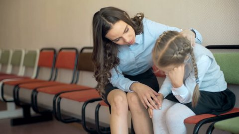 A female teacher sits consoling a young school sad girl in the corridor