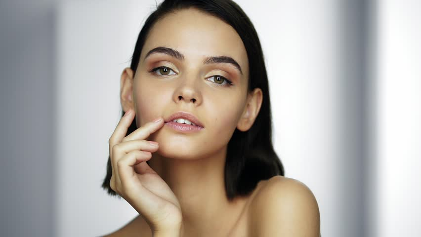 Beautiful healthy woman touching smooth skin on face. Youth and Skin Care Concept. Close up