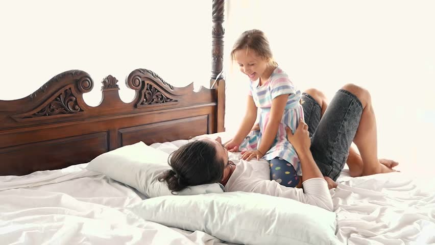 Happy Family Idyll Little Child Daughter Jump On Father Arms And They Fall On A Bed