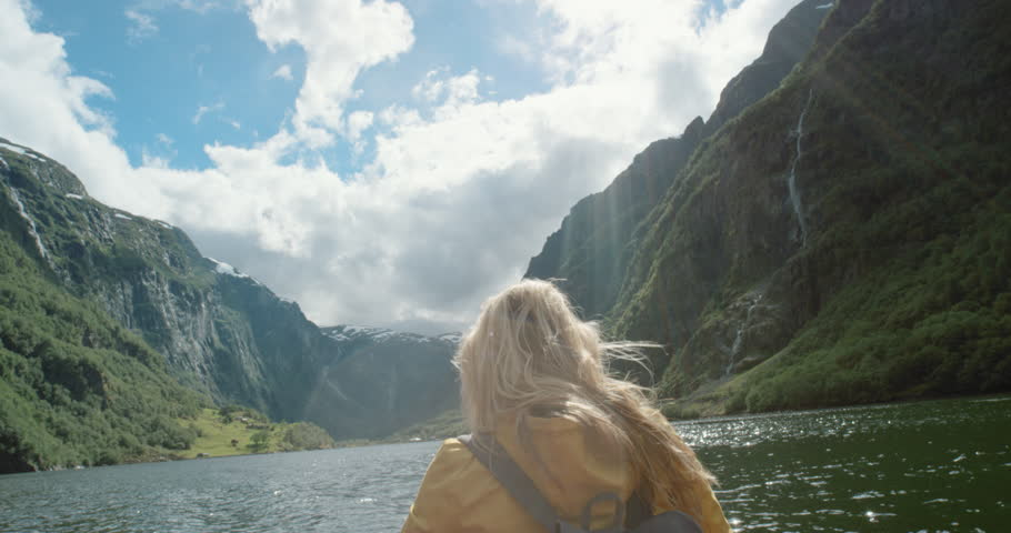 Woman sitting in boat on Fjord Norway hair blowing in wind traveling towards scenic landscape nature background view enjoying vacation travel adventure | Shutterstock HD Video #25058705