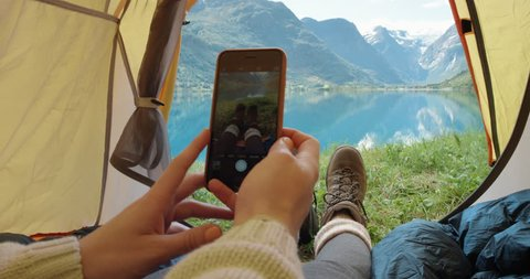 Camping woman lying in tent taking photo of feet with smart phone Close up of Girl wearing hiking boots relaxing on vacation POV Norway