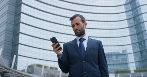 A businessman answering the phone, send messages and smiles for the beautiful job news and in the background you see a skyscraper. Concept: technology, telephony, business trips, business, wall street