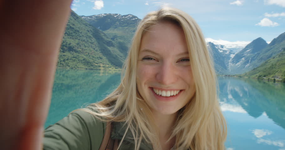 Beautiful woman taking selfie video using smartphone outdoors Girl sharing photograph on social media with mobile phone enjoying Norway vacation travel adventure | Shutterstock HD Video #25088603