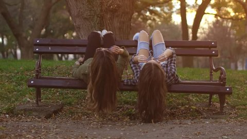 Two funky girlfriends having fun and lying upside down on a bench in park.